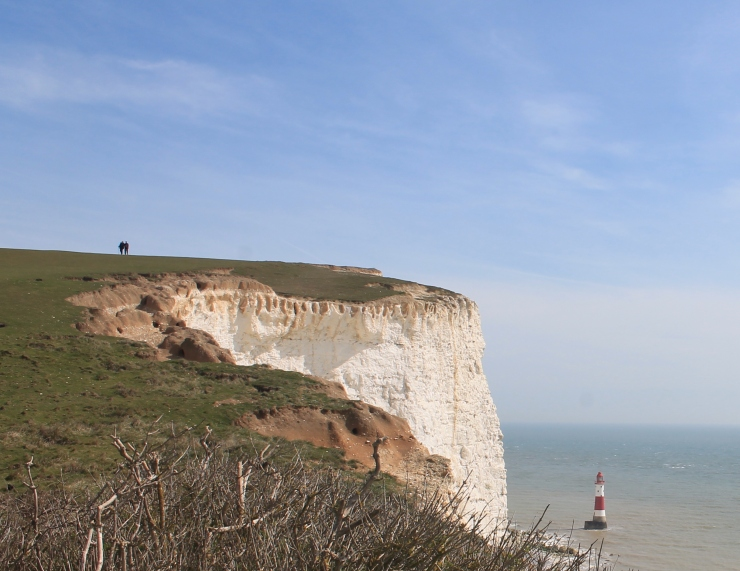 A closer shot of Beachy Head with the light house to the right. The silhouettes of two people walking can be seen at the top of the cliff.